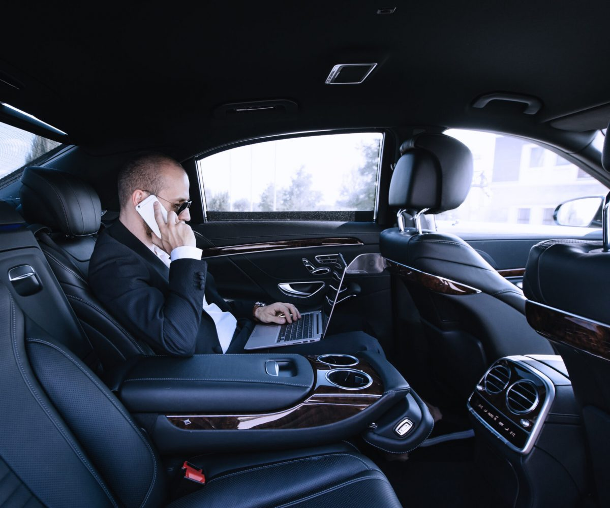 Confident young businessman working on his laptop and talking on the phone while sitting on the back seat of luxury car