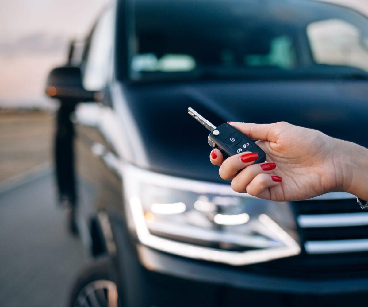 Woman is holding car keys in front of minivan